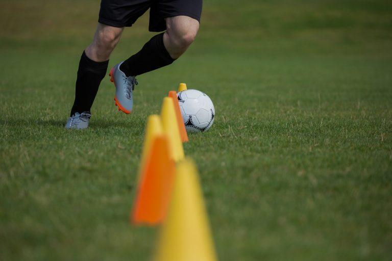 Soccer player dribbling through cones